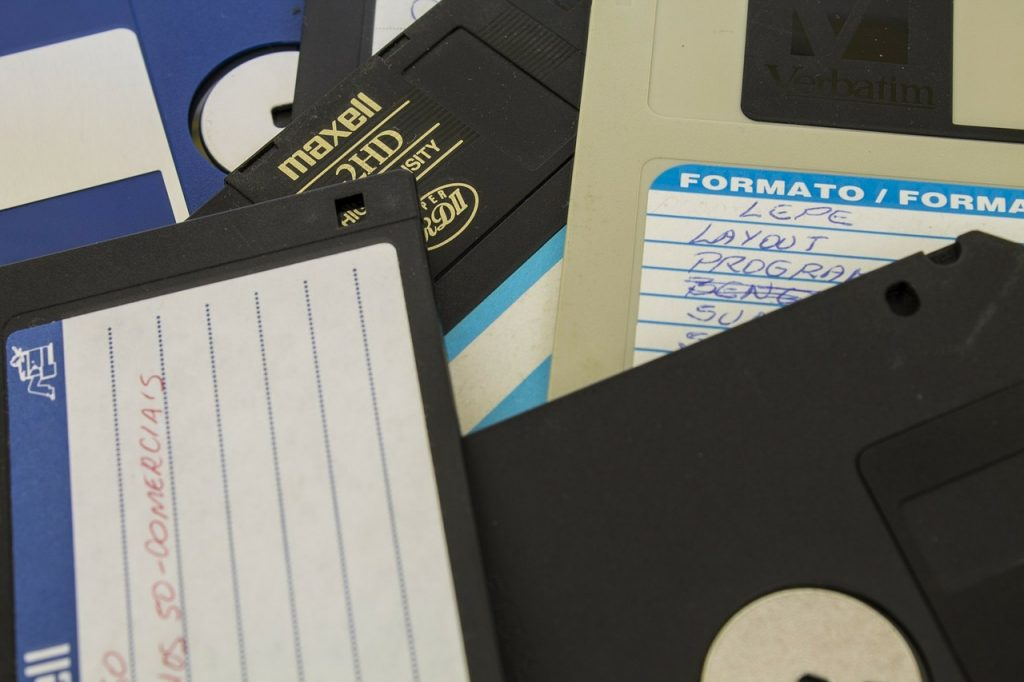 Pile of 3.5 inch floppy disks with blank and ambiguous labels