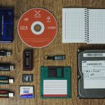 thumb drives, cd rom, hard drives, 3.25 inch floppy disk, and other storage samples arranged on a desk
