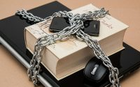 laptop, book, and cell phone, stacked and bound by a chain